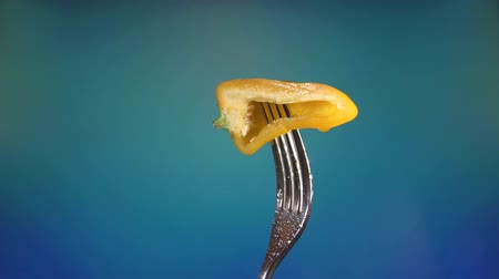 villa : fork with fresh yellow chopped pepper, spinning blue background