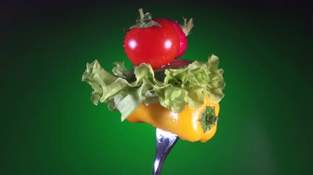 zeller : fork with yellow pepper slices of cucumber, radish and tomato lettuce rotates green background