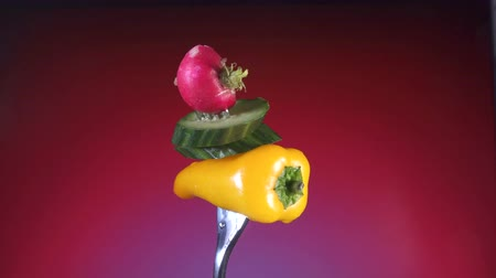 healthyfood : fork with yellow pepper slices of cucumber and radish, a red background rotates