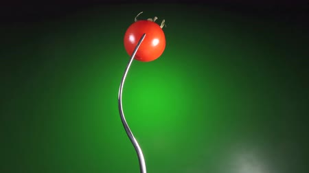 pepinos : fork with red fresh tomato, rotation green background Vídeos