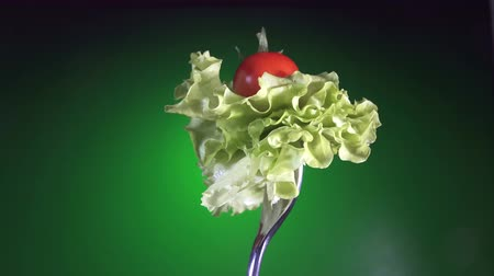 olive wood : fork with red fresh tomato and lettuce, rotation green background