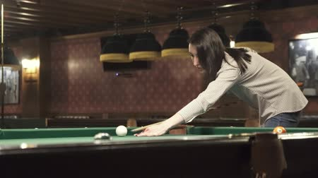 brunette girl playing billiards