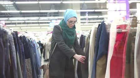 beautiful girl in hijab picks clothes in store