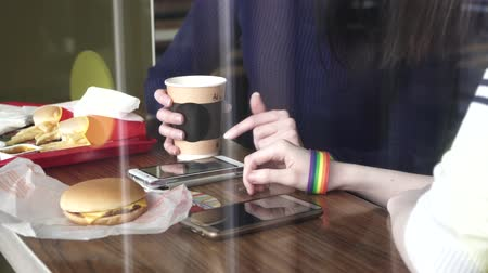 womens hands in the cafe using a phone with LGBT bracelets