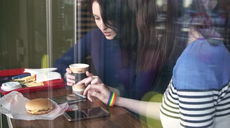 two girls in a cafe communicate and use phones with LGBT bracelets