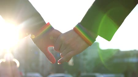 Two hands stretch to each other with LGBT bracelets against the backdrop of the street Wideo