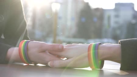 hands of a young couple with LGBT bracelets on the background of the street, behind a table