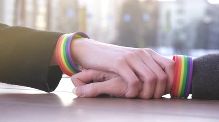 One hand reaches for the other with LGBT bracelets on the background of the street, at the table