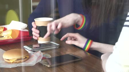 womens hands in the cafe using a phone with LGBT bracelets close up
