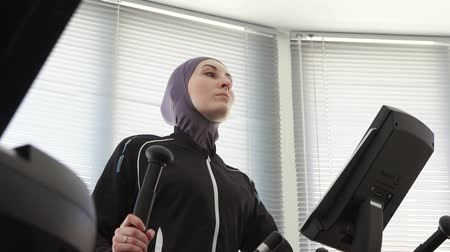 pretty girl in hijab on a sports simulator step