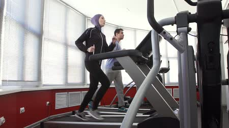 athlete woman wearing a hijab on a running simulator and a man in a gym Wideo