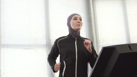 athlete girl in hijab on a running simulator Wideo