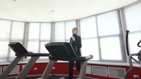 girl in hijab on running simulator