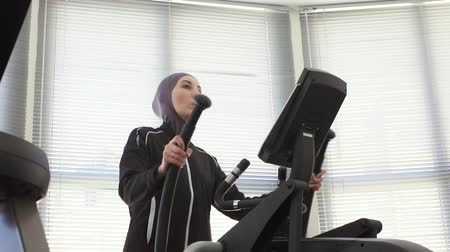 pretty girl in hijab on a sports fitness machine Wideo