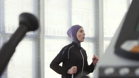 athlete girl in hijab on a running simulator slow mo Wideo