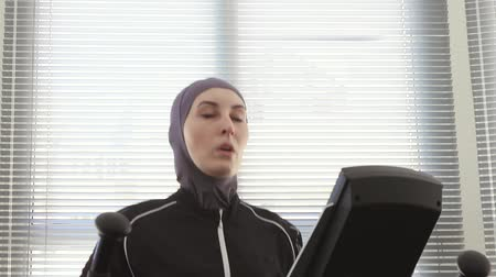 portrait of an athlete woman wearing a hijab on a step simulator in a gym