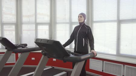 girl in hijab, walking warm-up in gym