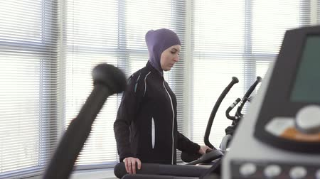girl in hijab, walking warm-up on a running simulator in the gym, fitness training
