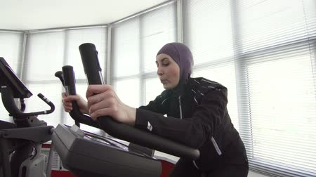 woman athlete in sports hijab on bike simulator Wideo