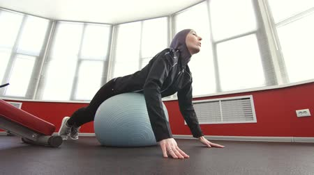 girl in hijab on fitness ball in gym Wideo