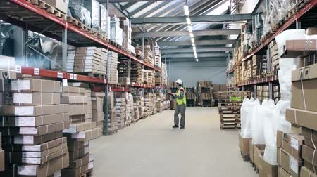 warehouse worker protection equipment walks by warehouse Wideo