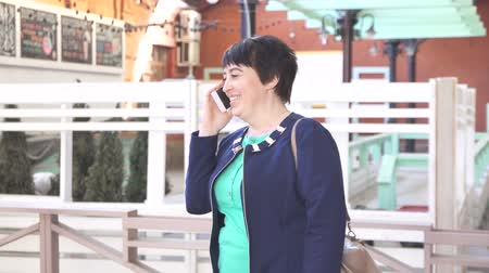 feminity : woman over 40 years old talking on the phone urban landscape Stock Footage