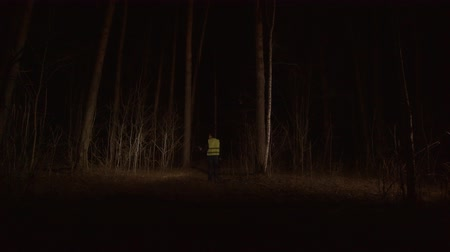 dead forest : single man with a lantern in the forest in uniform