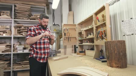 chisel : man carpenter in a shirt with a beard uses tools in the workshop Stock Footage