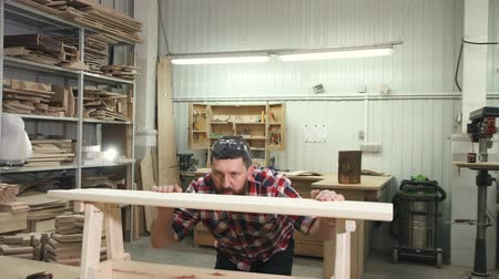 sierra circular : carpenter working in a shirt with a beard in the workshop makes a wooden bench Archivo de Video