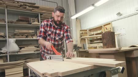 práce ze dřeva : man carpenter with a beard in a shirt with a circular saw on wood in the workshop Dostupné videozáznamy