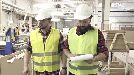 szállító : two workers in reflective waistcoats and helmets at the furniture factory