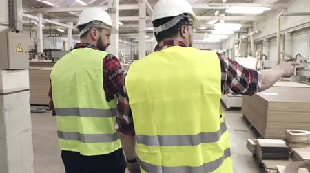 szállító : two workers talking in green waistcoats and helmets at a furniture factory among machines