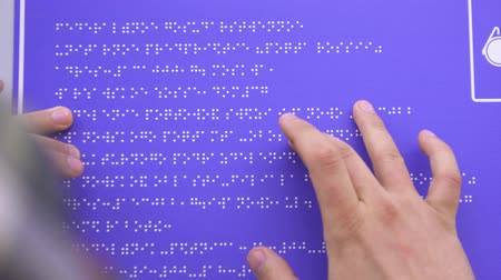 impaired : hands of a blind man in a shirt reading a braille font on a building sign Stock Footage