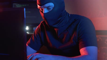 balaclava : an anonymous man in a balaclava at a computer types
