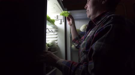 refusal to eat : woman 40 years old during a diet looks in the refrigerator Stock Footage