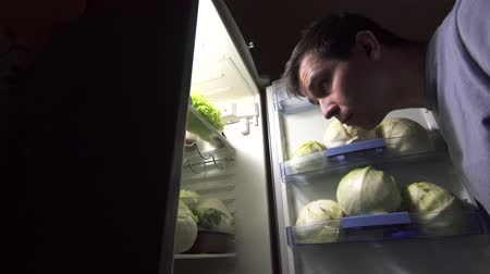 lehká váha : sad man during a diet looks in the refrigerator