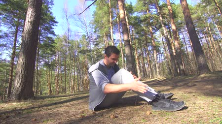 şişme : man during a jog gets a knee injury in a sunny forest