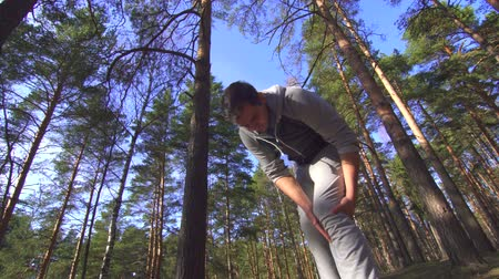 painéis : male athlete during a jog gets knee injury in a sunny forest