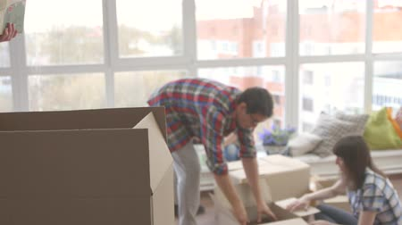 belongings : happy family unpacks boxes of things Stock Footage