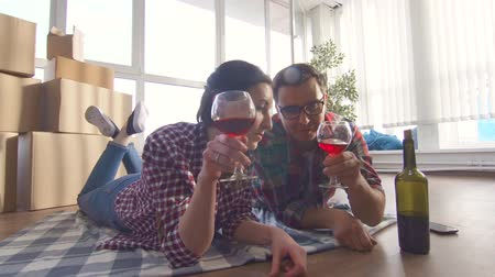 adega : young couple lies on the floor drinking wine and notes moving into a new apartment
