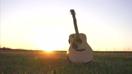 strum : guitar in field at sunset