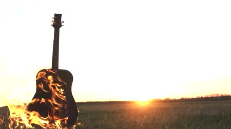 освещенный : Burning guitar on fire in the field