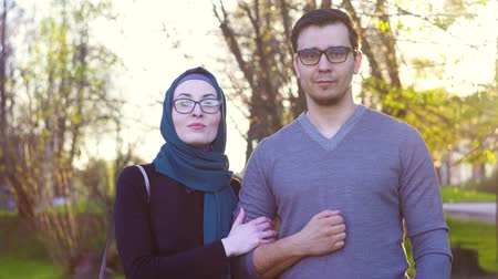 parentes : cute young couple in glasses looks at camera in park, sunny