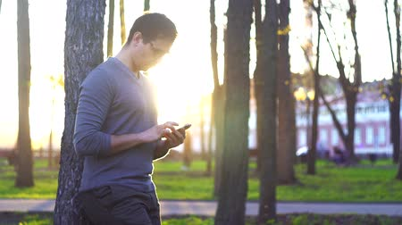parkland : man in the park at sunset against the backdrop of the cityscape using a smartphone