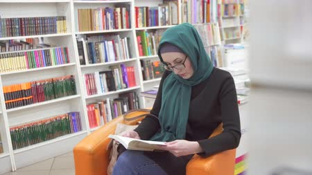biblioteca : girl in hijab reading book in library