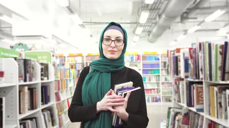 biblioteca : pretty girl in hijab with books in hands in a bookshop Stock Footage