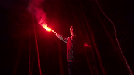 sos : a man holds in his hand a signal fire in the forest, Stok Video