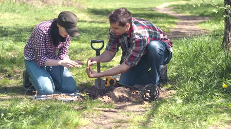 hoard : girl and man treasure Hunters digging up old coins found in the Park with metal detector Stock Footage