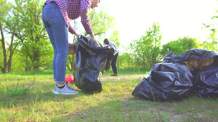 discarded : mom and teen daughter collect garbage in plastic bags in park concept
