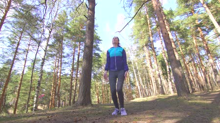 gumka : brunette girl makes a workout in a sunny forest